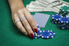 A menina na tabela do pôquer está guardando microplaquetas Fotografia de Stock