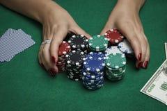 A menina na tabela do pôquer está guardando microplaquetas Fotografia de Stock Royalty Free