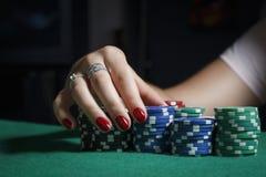 A menina na tabela do pôquer está guardando microplaquetas Fotos de Stock Royalty Free