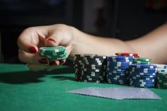 A menina na tabela do pôquer está guardando microplaquetas Imagens de Stock Royalty Free