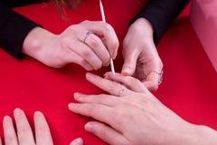 A menina na tabela faz seu tratamento de mãos imagem de stock royalty free