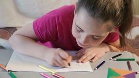 A menina na tabela tira em lápis coloridos vídeos de arquivo