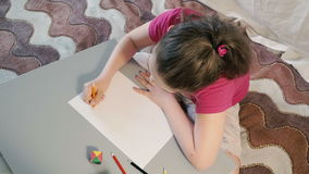 A menina na tabela tira em lápis coloridos filme