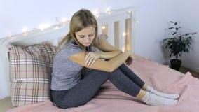Menina na tristeza que senta-se em uma cama video estoque