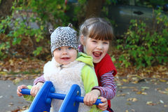 A menina na veste branca e a irmã jogam no velomotor Foto de Stock Royalty Free