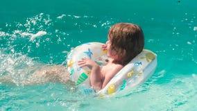 A menina nada na associação no círculo inflável ativamente agitando o pé sob a água vídeos de arquivo