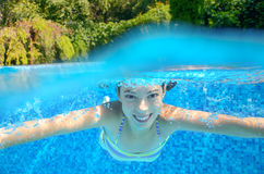 A menina nada na piscina, underwater e acima da vista Imagens de Stock