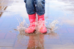 A menina nas botas cor-de-rosa que saltam nas poças fotografia de stock