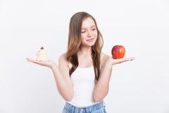 Menina nas calças de brim com maçã e queque Imagens de Stock