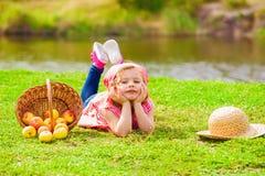 Menina nas calças de brim e em uma camisa perto de um rio com maçãs Foto de Stock