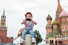 Menina nas calças de brim e no tampão perto do assento do Kremlin Imagem de Stock Royalty Free