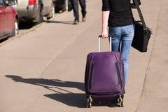A menina nas calças de brim está na estrada com uma mala de viagem imagens de stock