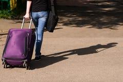 A menina nas calças de brim está na estrada com uma mala de viagem imagem de stock royalty free