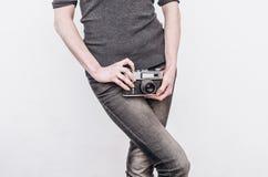 A menina nas calças de brim guarda uma câmera velha do filme do vintage nos quadris imagem de stock royalty free