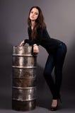 Menina nas calças de brim que estão perto de um tambor do ferro Fotografia de Stock Royalty Free