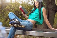 Menina nas calças de brim que lê um livro no banco Imagem de Stock Royalty Free