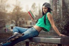 Menina nas calças de brim que lê um livro no banco Fotos de Stock Royalty Free