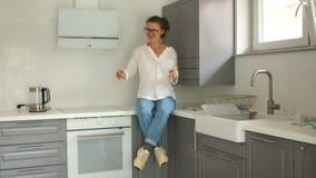 Menina nas calças de brim que sentam na bancada sua cozinha nova Alojamento alugado, transações dos bens imobiliários vídeos de arquivo