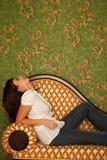 A menina nas calças de brim senta-se no sofá e olha-se a parede Foto de Stock Royalty Free