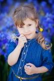 A menina nas calças de brim veste-se com as íris nas mãos Imagem de Stock