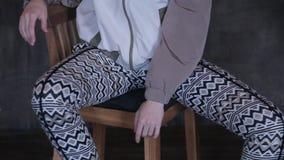 A menina nas calças justas senta-se em uma cadeira e em um levantamento vídeos de arquivo