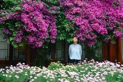 Menina nas flores de spectabilis da buganvília Fotos de Stock Royalty Free