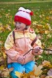 Menina nas folhas de outono Fotografia de Stock Royalty Free