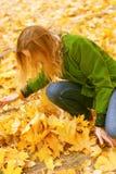 Menina nas folhas de outono Fotos de Stock Royalty Free