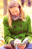 Menina nas folhas de outono com um caderno Imagens de Stock