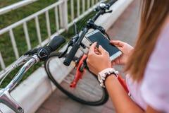 A menina nas mãos guarda o telefone, seleciona a aplicação do mapa em linha ao Internet, busca para uma rota em torno do foto de stock royalty free