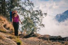 Menina nas montanhas com uma trouxa pesada Imagem de Stock