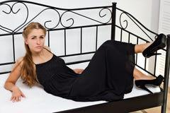 Menina nas sapatas de vestido pretas que encontram-se na cama Imagem de Stock Royalty Free