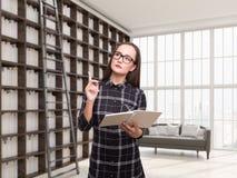 Menina Nerdy nos vidros em sua biblioteca da casa Imagens de Stock Royalty Free