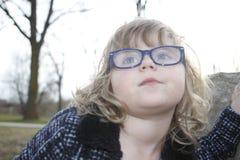 A menina nerdy nova com vidros envelheceu 3-5, cabelo louro, olhos azuis Retratos da criança em idade pré-escolar Imagens de Stock
