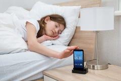 Menina no alarme adormecido do telefone celular da cama imagens de stock