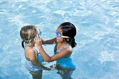 Menina no amigo da ajuda da piscina com óculos de proteção Fotografia de Stock