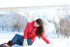 A menina no ar fresco, sentando-se na neve branca Imagens de Stock