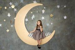 Menina no assento na lua grande Sonhar pequeno da menina Imagem de Stock