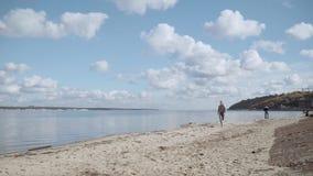 A menina no assunto corre ao longo do Sandy Beach A menina está em uma corrida Uma moça corre ao longo da costa O louro dentro filme