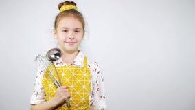A menina no avental como um cozinheiro chefe profissional olha na câmera Fundo para o texto vídeos de arquivo