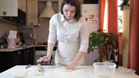 A menina no avental desenrola a massa da pizza com um pino do rolo Cozinhando a pizza em casa video estoque