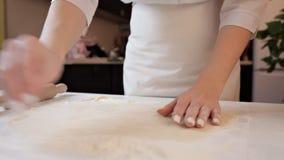 A menina no avental desenrola a massa para a pizza com um pino do rolo A menina desloca a massa, polvilha-a com filme