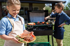 Menina no avental que guarda a placa com bifes frescos quando seu irmão que prepara a carne na grade fotografia de stock royalty free