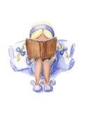 A menina no azul está lendo o livro Fotografia de Stock Royalty Free