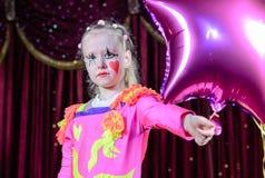 Menina no balão dado forma Costume Holding Star do palhaço Fotografia de Stock Royalty Free