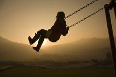 Menina no balanço no por do sol Imagem de Stock