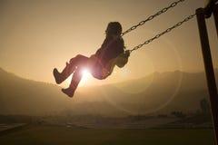 Menina no balanço no por do sol Imagens de Stock