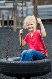 Menina no balanço do pneu. Foto de Stock Royalty Free