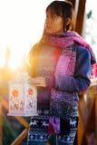 Menina no balcão fora durante o por do sol que guarda a lanterna da vela Foto de Stock
