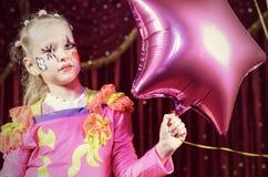 Menina no balão dado forma Costume Holding Star do palhaço Imagens de Stock Royalty Free